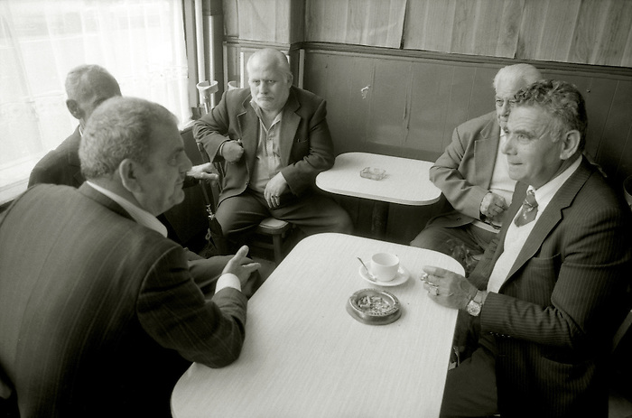 A group of old men sit around a cafe table in North London, talking, drinking and smoking.