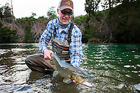 David Thompson admires a Rio Rivadavia brown trout while fishing in Patagonia, Argentina.