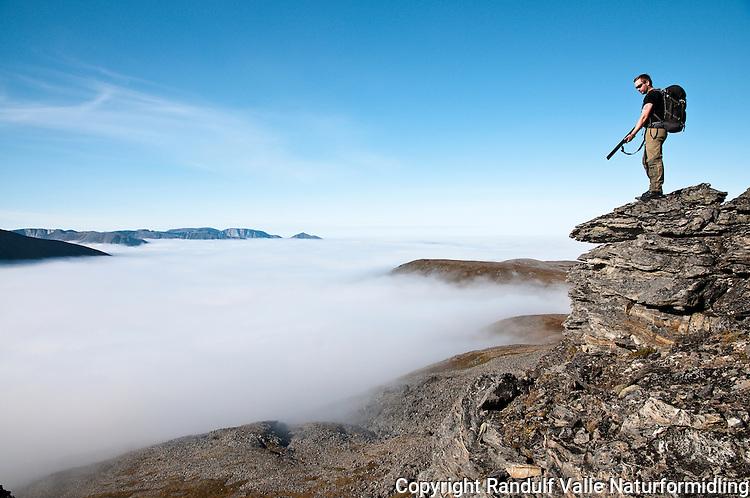 Jeger ser at lavereliggende deler av Sørøya dekkes av havskodde. ----- Hunter sees that lover parts of Sørøya are covered in mist.