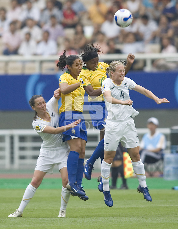 Brazil midfielders (7) Daniela and (2) Ester battle New Zealand midfielder (4) Katie Hoyle for a header. Brazil (BRA) defeated New Zealand (NZL) 5-0 in their  FIFA Women's World Cup China 2007 Group D opening round match at Wuhan Sports Center Stadium in Wuhan, China on September 12, 2007.