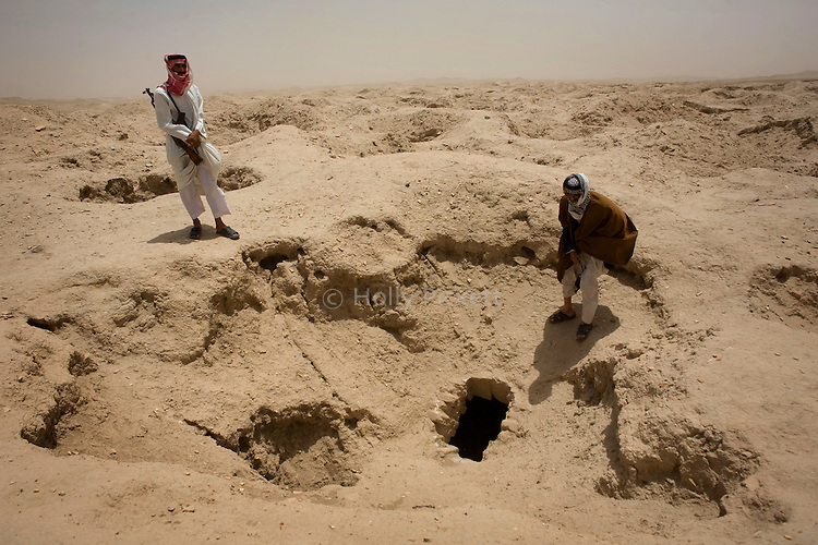 Local Bedouin tribesmen Tellaf Jahad Shahein, right, and his son Rathi Shahein at a looted Sumerian tomb, one of hundreds of illegal digging sites at the ancient site Dubrum, a Sumerian city buried near the village of Dhahir in southern Iraq, May 21, 2010. Iraq's unguarded archeological sites have fallen prey to looters.