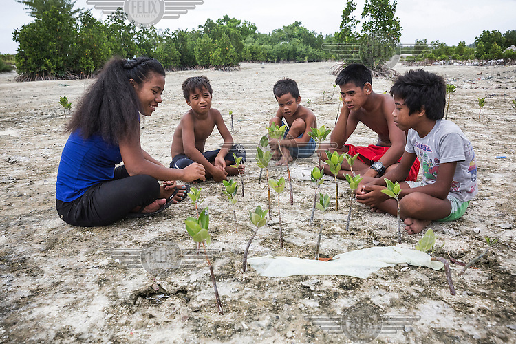 Tinaai Teaua, a member of Kiribati Climate Action Network (KiriCAN), explaining to village children the important role of mangroves in protecting the country's shores from coastal erosion.