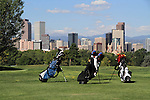 Three golf bags ready for use at tee-off, City Park Golf Course with downtown skyline and Rocky Mountains behind, Denver, Colorado, USA