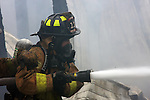A woman firefighter putting water on a fire