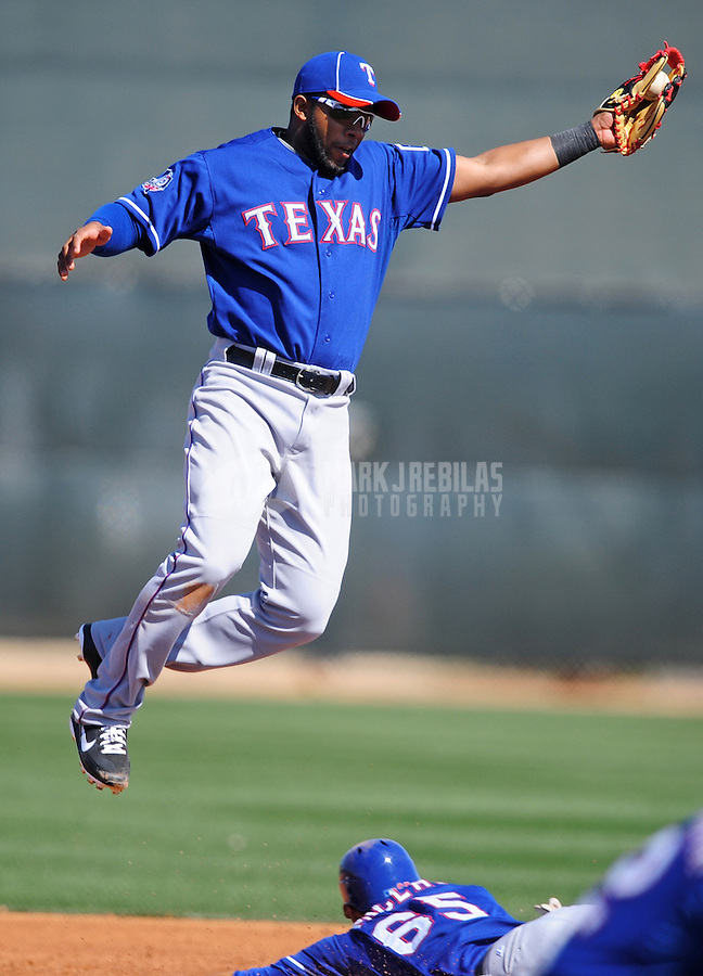 Mar. 2, 2012; Surprise, AZ, USA; Texas Rangers shortstop Elvis Andrus leaps as he catches the ball during an intrasquad game on the practice fields at Surprise Stadium.  Mandatory Credit: Mark J. Rebilas-.