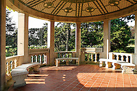Circular limestone garden loggia with carved limestone benches, columns and curved lattice ceiling.
