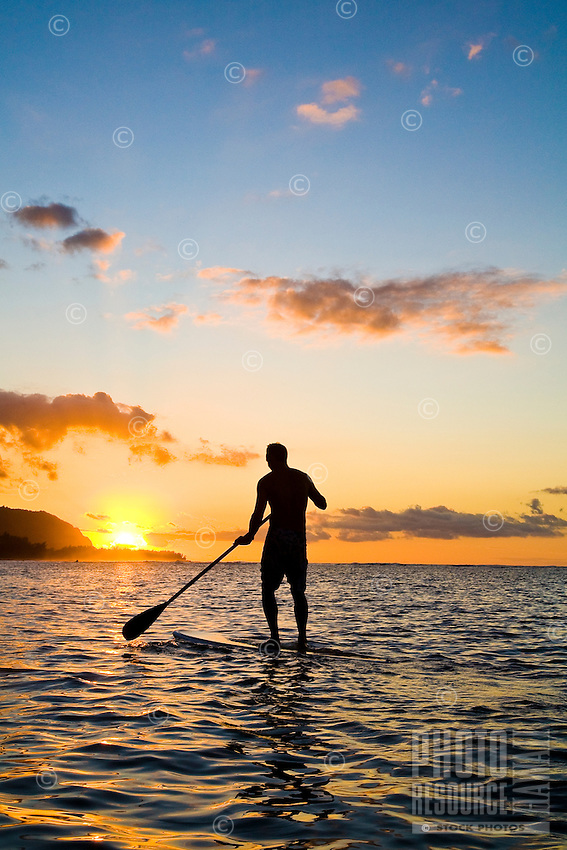 Young man standup paddling (SUP) at sunset off the shores of Mokuleia