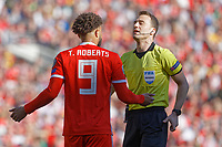Referee Felix Zwayer (R) speaks to Tyler Roberts of Wales during the UEFA EURO 2020 Qualifier match between Wales and Slovakia at the Cardiff City Stadium, Cardiff, Wales, UK. Sunday 24 March 2019