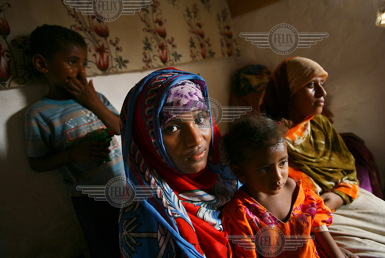 Ruqia (left) and Seloua (right) sit with Ruqia's two children, Soumaia, aged 2, and Herhan, aged 4, in Seloua's house. Both women, now aged 18, were married at 14.