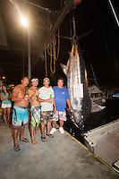 Bomboy Llanes (in blue shirt), captain of the fishing boat Lana Kila, stands with his crew next to a Pacific blue marlin grander at Honokohau Harbor, Kailua-Kona, Big Island.