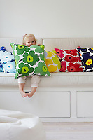 A little girl plays with the Marimekko cushions on the banquette in her playroom