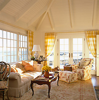 The sunny living room has large windows which afford it spectacular panoramic views over the water