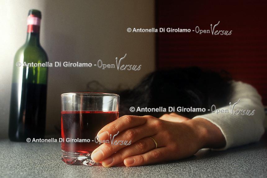 Donna alcolista beve un bicchiere di vino rosso..Woman drink a glass of red wine....