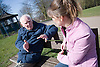 Older man and his carer sitting on a bench talking,