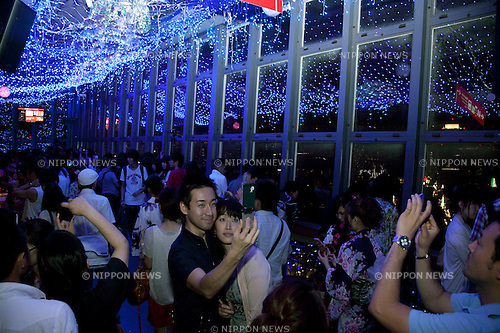 July 7, 2012, Tokyo, Japan - Visitors to the main observatory of Tokyo Tower contemplates the LED lights that illuminate the place, lighting represent Orihime (the female figure), white lights represent Hikoboshi  (the male figure) and blue light the Milky Way in commemoration of the festival of Tanabata. The annual celebration of Tanabata in Japan and has been held since the Edo era. It celebrates the meeting of two lovers Orihime and Hikoboshi, according to legend the Milky Way separates these lovers, and may only meet once a year on the seventh day of the seventh month of calendar. (Photo by Rodrigo Reyes Marin/AFLO)