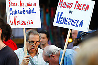"Demonstrators  supports President Maduro holds a poster entitle ""Stop Spanish Government in Venezuela. Get out of Venezuela""."