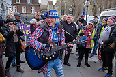 An anti-Brexit campaigner with a guitar taunts Brexit supporters demonstrating outside the Houses of Parliament as MPs vote to extend the Article 50 deadline for an agreed withdrawal deal with the EU.  Westminster, London.