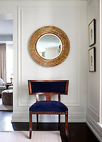 A gilt framed mirror hangs on the wall above a wood chair with blue upholstery.
