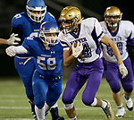SIOUX FALLS, SD - OCTOBER 25: Sam Kruger #14 From Winner looks to escape the grasp of Isaac Niemeyer #58 from Sioux Falls Christian in the first half of their 11B playoff game Thursday nigh at Bob Young Field in Sioux Falls.(Photo by Dave Eggen/Inertia)