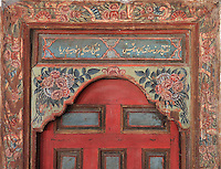 Painted decorative door in the Prayer hall of the Helveti Tekke or Teqe e Helvetive, a Bektashi Sufi shrine of the Helveti sect built in the 15th century and rebuilt by Ahmet Kurt Pasha in 1782, with mihrab on the far wall, in Berat, South-Central Albania, capital of the District of Berat and the County of Berat. The ceiling is decorated in the Baroque style adopted by Islamic art and 14 carat gold has been used. The tekke is composed of a square prayer hall, an external portico (with columns from Appolonia) and a room which housed the mausoleum of Ahmet Kurt Pasha and his son. On the inner walls are 8 frescoes of houses, muslim religious buildings and gardens. Picture by Manuel Cohen