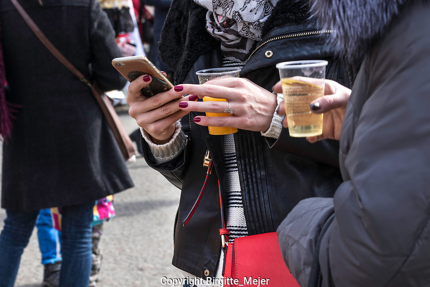 Female hands, with purple nail polish, having her phone in right hand and a plastic cup with Juice in the other checking her mobile phone messages