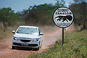 Wildlife crossing X-ing traffic warning sign showing a giant anteater on a dirt road in the Southern Pantanal. Mato Grosso do Sul, Brazil.