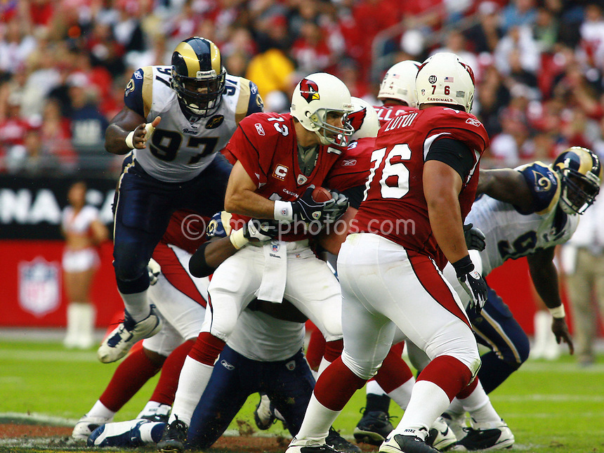 Dec 07, 2008; Glendale, AZ, USA; St. Louis Rams defensive tackle La'Roi Glover (97) leaps in the air to help sack Arizona Cardinals quarterback Kurt Warner (13) in the third quarter of a game at University of Phoenix Stadium.  The Cardinals won the game 34-10 to clinch the NFC West division title.  Mandatory Credit: Chris Morrison-US PRESSWIRE