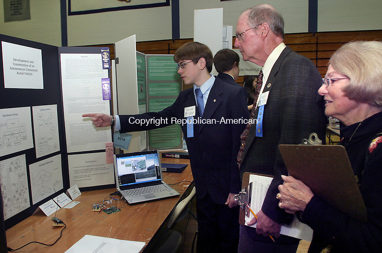 HAMDEN, CT.- 12 MARCH 2009-031209DA02-Matthew Petroff, left, 10th grade student of Taft School in Watertown speaks to judges, John Kendall, center, Ruth Mensing about his science project on Development and Construction of an Autonomous Unmanned Aerial Vehicle during the Finalists in the Connecticut State Science fair. The event was held at Quinnipiac University gymnasium in Hamden Thursday.<br />  Darlene Douty Republican-American
