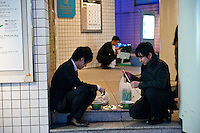Stranded salarymen eating instant ramen. Shinagawa, Tokyo, 11 March 2011. After a huge earthquake in north-east Japan several million people in Tokyo struggle to return home.