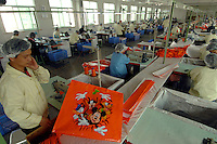 Workers make Disney woven plastic carrier bags at the Richall factory in Dongguan, Guangdong province, China.. The woven plastic bags can be used many times and are seen as environmentally friendly. The company makes plastic bags for several clients including Disney and Sainsbury's..