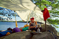 Algonquin Park, Ontario, Canada, July 2006. Jillian prepares a dinner of dried outdoor food complemented with wild mushrooms and blueberries in one of the campsites on Opeongo Lake. The Algonquin Provincial Park consists of many lakes that can be explored by canoe and which are connected by portages. Photo by Frits Meyst/Adventure4ever.com