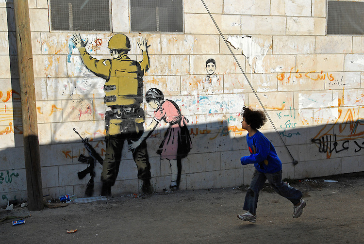 A girl passes by a graffiti by British street artist Banksy, at the Palestinian refugee camp of Dheisheh, West Bank.