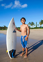 A beaming young local boy with his surfboard at Hanalei Beach, Kaua'i.