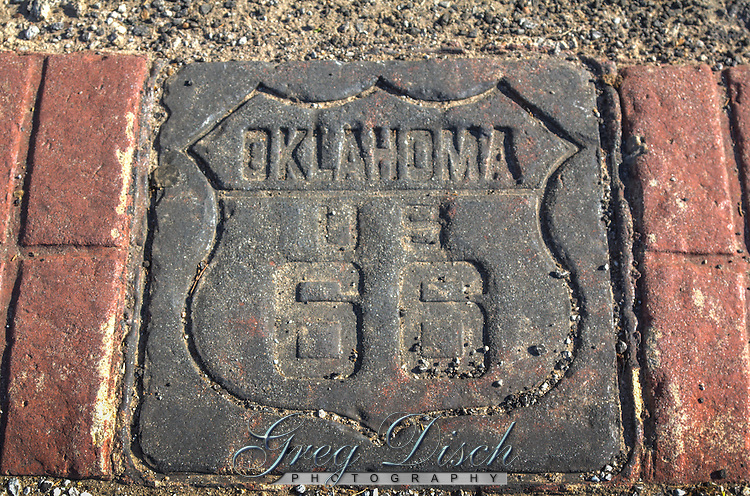 Route 66 markers are placed every few feet along the sidewalk on 11th street in Tulsa Oklahoma.