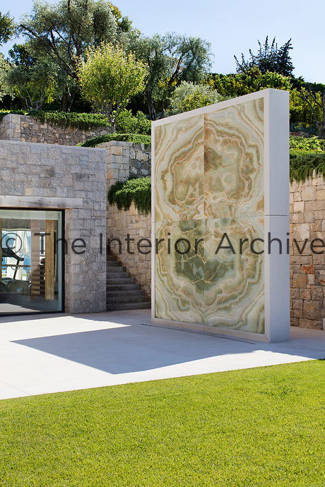 A stone installation dominates the terrace outside the living area.