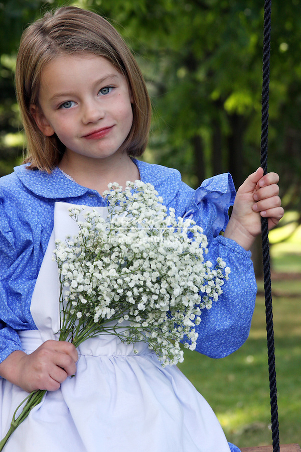 A young girl holding flowers on a swing