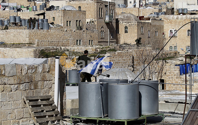 An Israeli soldier removes the Israeli flag from a house as dozens of settlers were evacuated by Israeli security forces from two homes in the heart of the West Bank city of Hebron on January 22, 2016, the day after they entered the buildings sparking violent clashes over disputed ownership claims. Israeli troops forcibly removed Jewish settlers from homes they said they had purchased from Palestinians in the occupied West Bank city of Hebron on Friday, prompting some right-wing Israeli lawmakers to threaten to withhold support for the government. Ministers and members of parliament from Prime Minister Benjamin Netanyahu's Likud party decried Defense Minister Moshe Yaalon's refusal to sign off on the settlers' occupation of the homes in Hebron, a city of high tension between Israelis and Palestinians. Photo by Wisam Hashlamoun