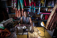 Uganda, Buikwe. WOW, solar system powering the television in Gertrude's home. Gertrude Nalule in her tailoring shop using solar light.
