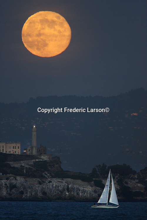 Full Moon over Alcatraz Island seen from Crissy Field in the Presido....11/6/06.{Photographed by Frederic Larson}...Full moon rises behind Alcatraz Island in the San Francisco bay as a small sailboat tacks back and forth at twilight.