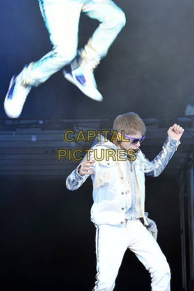 JUSTIN BIEBER.Performing live at the O2 Arena, London, England..March 17th, 2011.stage concert live gig performance music half length white jeans denim silver jacket singing sunglasses shades dancing.CAP/MAR.© Martin Harris/Capital Pictures.