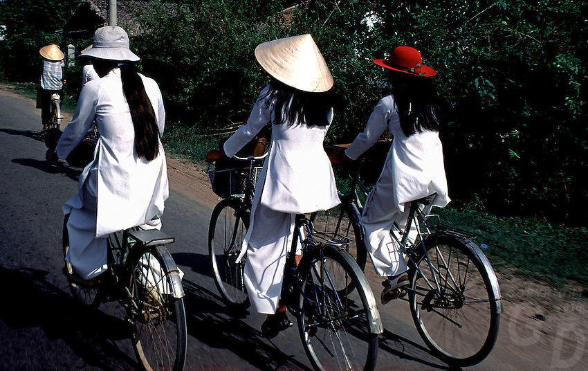 Girls on their bikes in in the Mekong Delta, note the different hats,Vietnam
