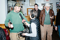 An NHPR reporter interviews Timmy Fortier (green), of Raymond, NH, before Ohio governor and Republican presidential candidate John Kasich speaks at a town hall campaign event at Raymond VFW Post 4479 in Raymond, New Hampshire, on Wed., Feb. 3, 2016.