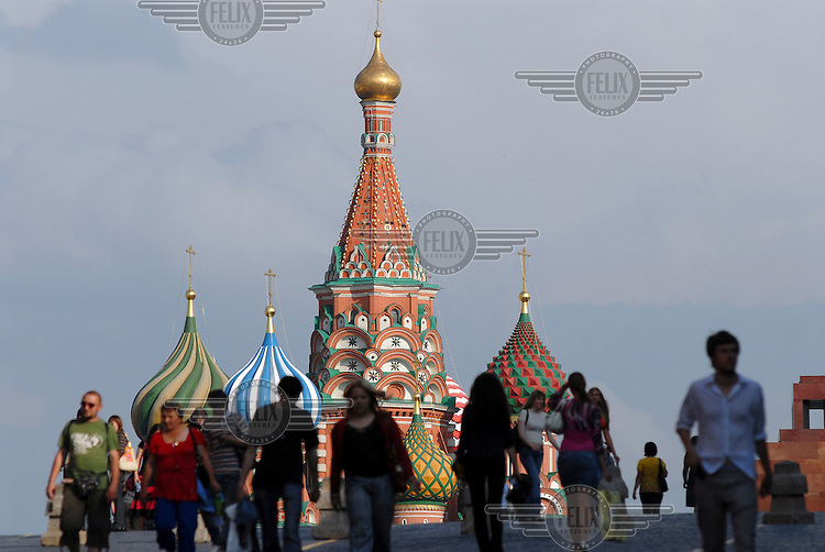 Tourists walk in front of St Basil's Orthodox Cathedral in Red Square.