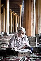 Muslim woman reading the Koran at the Jamia Masjid or grand mosque at midday in Srinagar as the main duty to observe the holy month of Ramadan. As the tradition is attended muslims has to fast from dawn to dusk, where they refrain from eating, drinking and smoking.