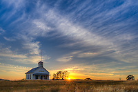 A sunset over an old schoolhouse in the Sierra foothills