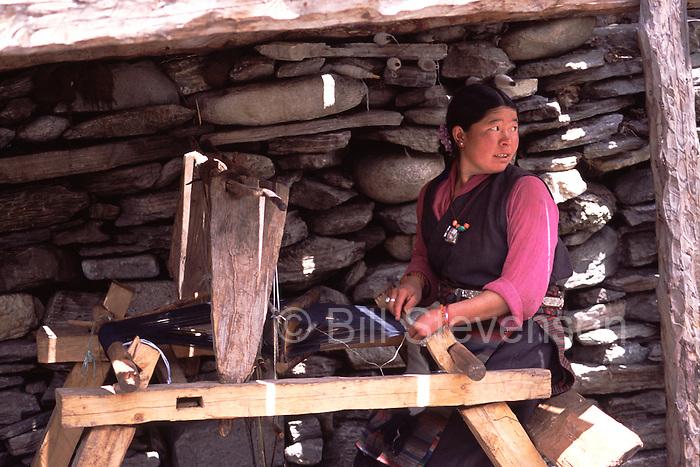 A Tibetan woman weaving on a traditional loom in Samagoan village in Nepal.