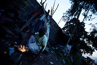 Brook, 12, takes care of the fire that will be used to cook dinner for his family, next to the shack where he lives in the center of Addis Ababa, Ethiopia on Wednesday June 06 2007.