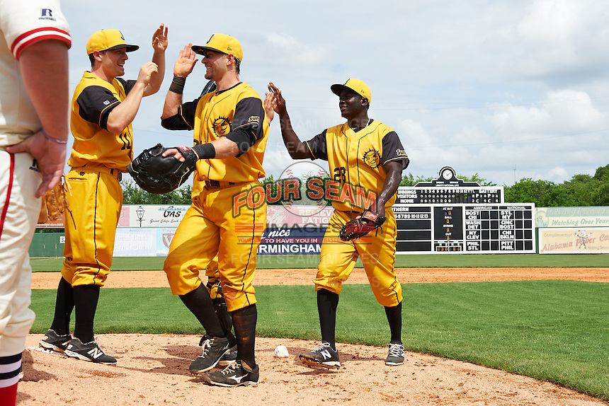 Jacksonville Suns Chadd Krist (11) high fives David Adams (35) and Juancito Martinez (28) after the 20th Annual Rickwood Classic Game against the Birmingham Barons on May 27, 2015 at Rickwood Field in Birmingham, Alabama.  Jacksonville defeated Birmingham by the score of 8-2 at the countries oldest ballpark, Rickwood opened in 1910 and has been most notably the home of the Birmingham Barons of the Southern League and Birmingham Black Barons of the Negro League.  (Mike Janes/Four Seam Images)