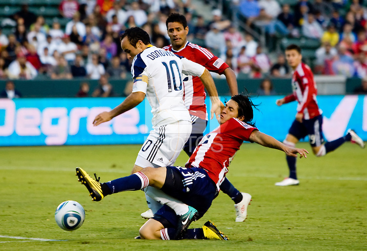 LA Galaxy midfielder Landon Donovan is tackled by Chivas USA defender Carlos Borja. The LA Galaxy beat Chivas USA 2-1 at Home Depot Center stadium in Carson, California on Sunday October 3, 2010.