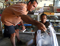 Koh Lanta, Thailand--David Karam (left), of Brewster, MA, purchases nails from a local hardware store to help reconstruct some of homes destroyed by the Tsunami in the village of Hua Laem on Koh Lanta island, Thailand.  Karam, who was on his way to Southeast Asia when the Tsunami hit, came to Koh Lanta to see how he could help.  01/19/05 © Julia Cumes / The Image Works